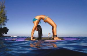 woman bent upside-down on purple surfboard